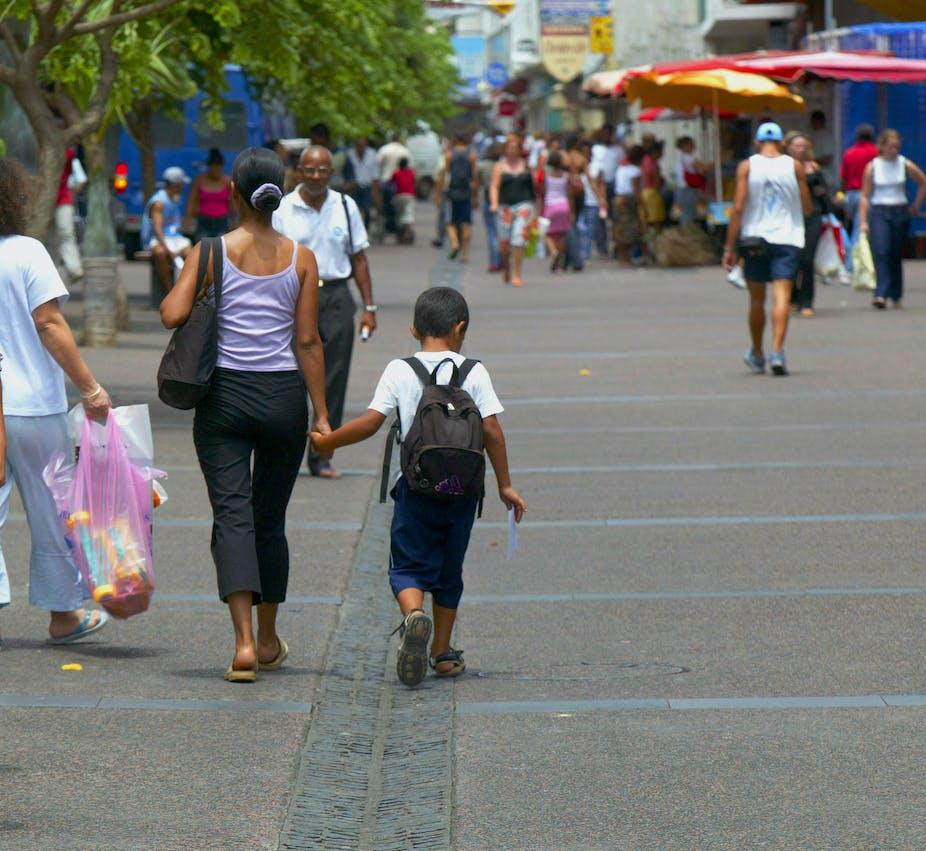 Une femme réunionnaise de face et des passants de do, sur un marché de Sait-Denis-de-la-Réunion