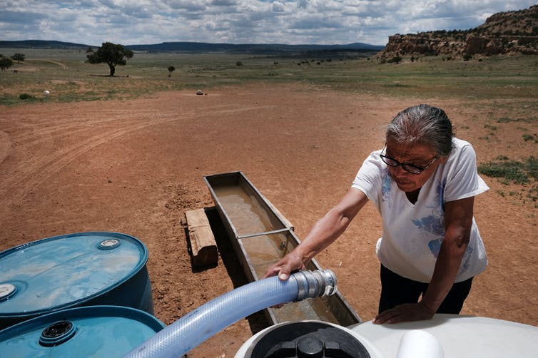 Woman connecting water hose to a tank in the desert.