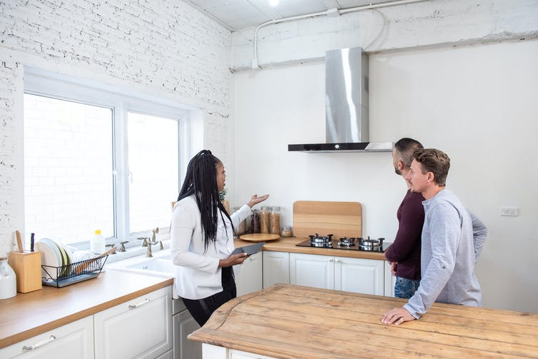 A real estate agent shows a young couple around an apartment.