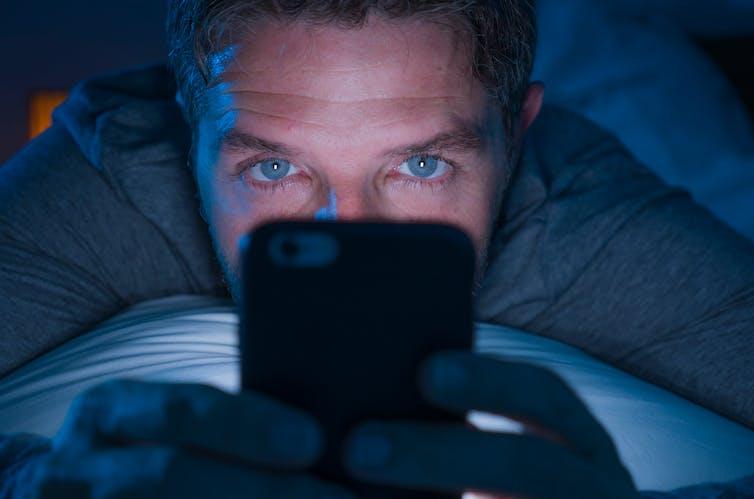 A man looks at his phone at night.
