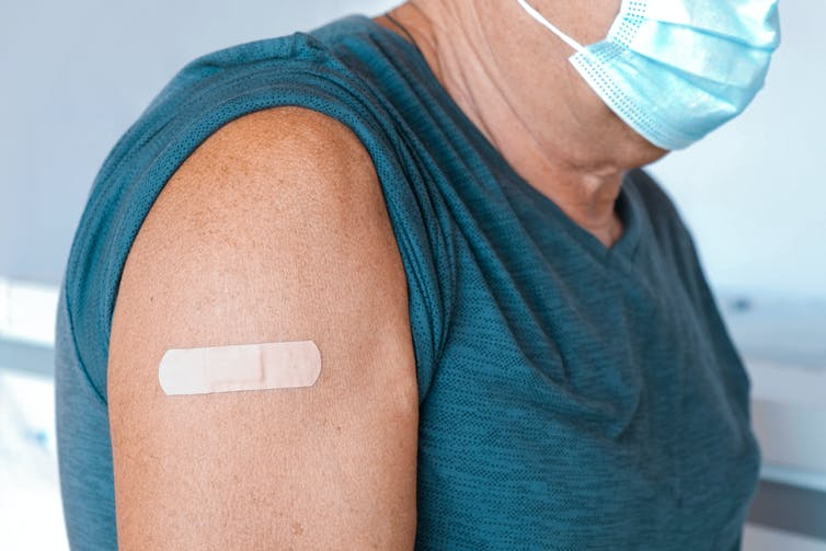 Older person's arm with a bandaid after being vaccinated.