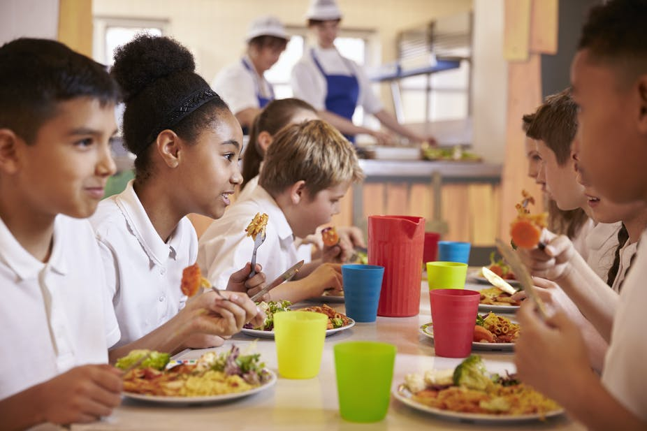 School children eating a nutritious lunch together in the cafeteria.