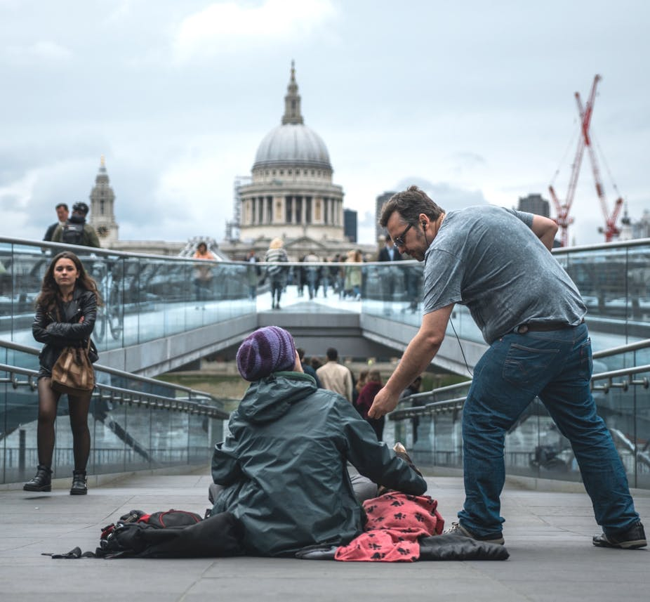 Man helping beggar woman with St Pauls in the background