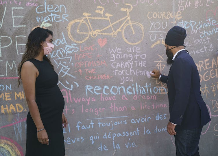 Jagmeet Singh Writing With Chalk On A Wall At A News Conference As His Wife Gurkiran Kaur Sidhu Looks On