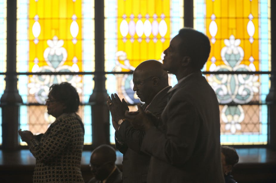 People standing in front of stained glass windows worship at John Wesley AME Zion Church in Washington, D.C.