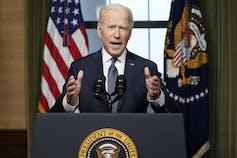 Biden speaks from behind a podium.