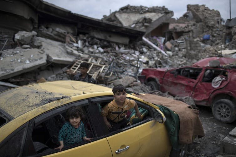 Children playing in a damaged car amidst a pile of rubble.