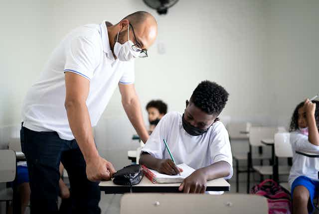 A mask-wearing teacher helps a Black student, who is also wearing a mask, on his classwork.