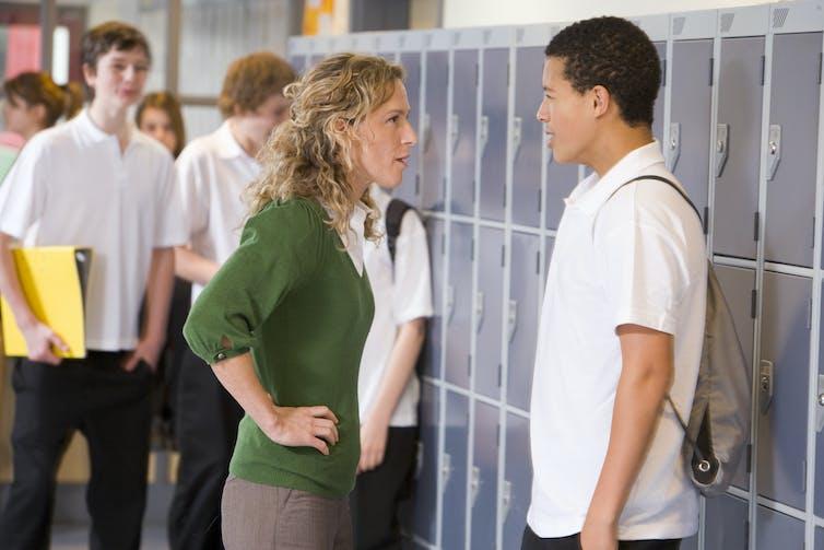 A white female teacher talks to a Black student in a hallway.