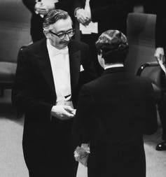 Hounsfield in tuxedo shaking hands with King facing away from camera