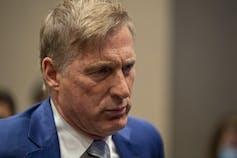 Bernier, in a blue suit, raises eyebrows.
