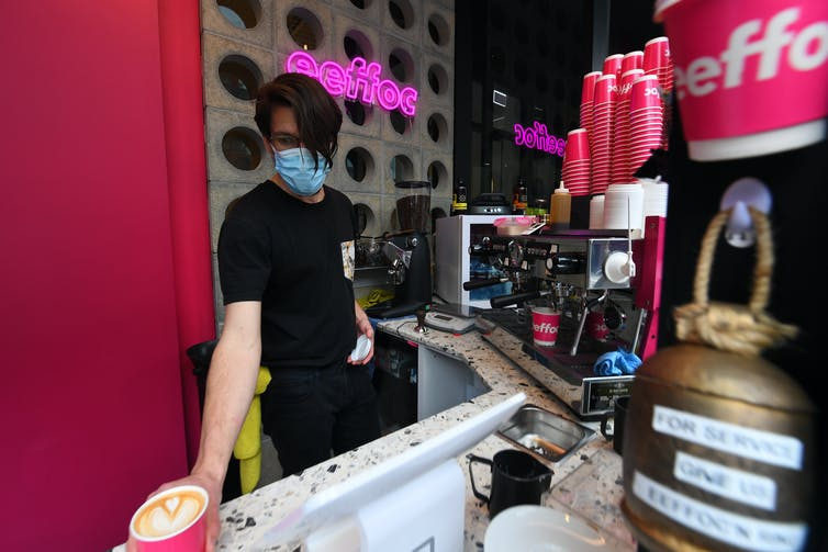 Cafe worker in a mask makes coffee.