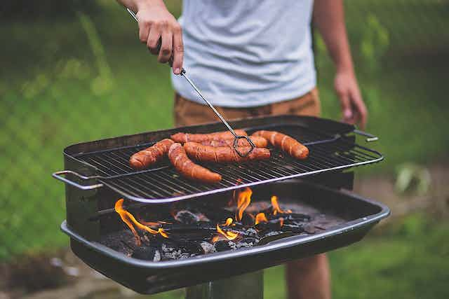 A person grills sausages on a barbecue