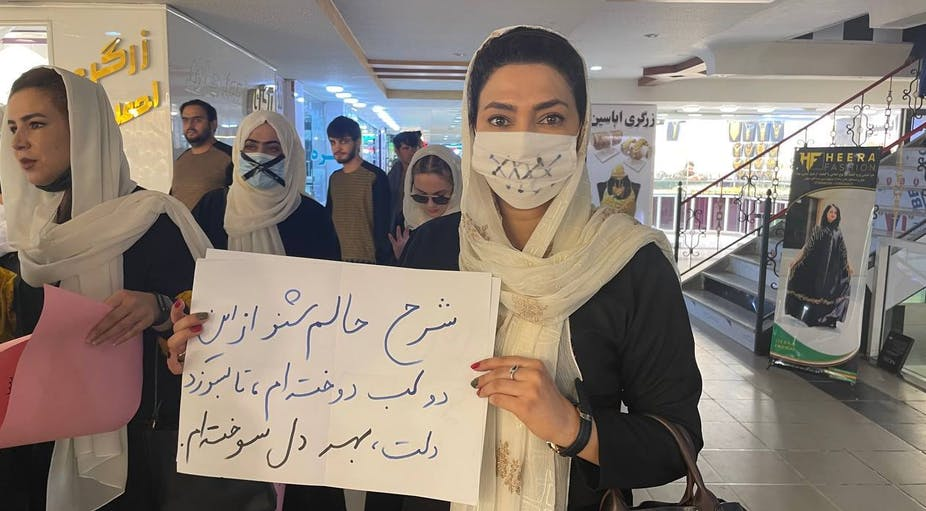 """Afghan women hold banners and put a tape on their mouths during a """"silent protest"""" for education rights in Kabul."""