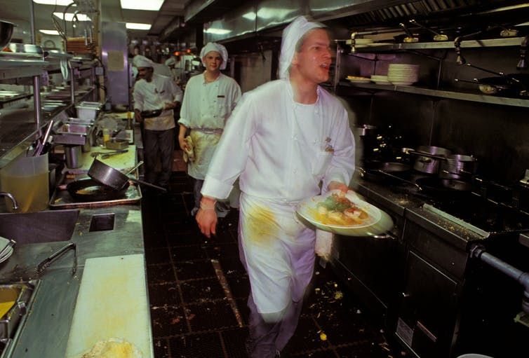 A sweating cook carries as plate past rows of ovens. The photo is shot with the cook slightly blurred, capturing the frenetic pace of the kitchen