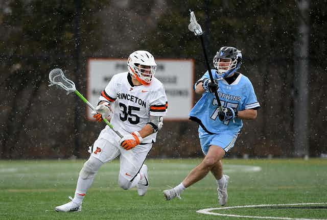 Two young white athletes play lacrosse on a field.