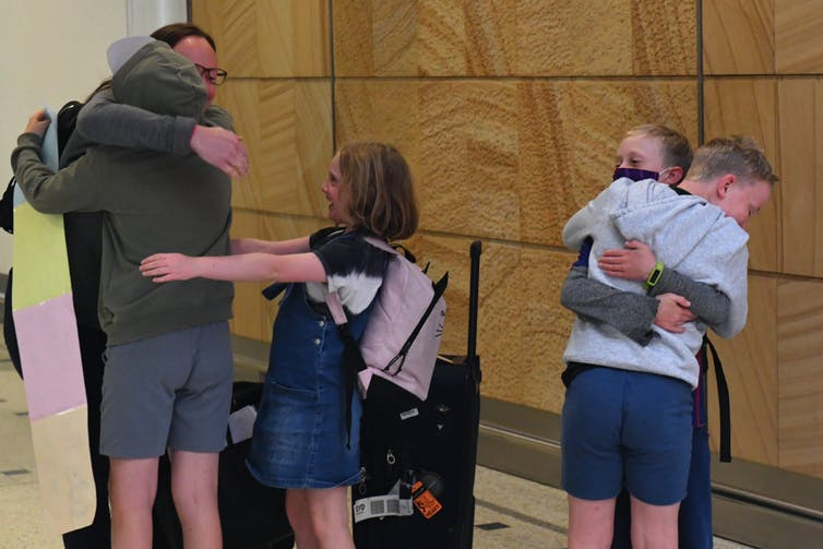 family hug at the airport