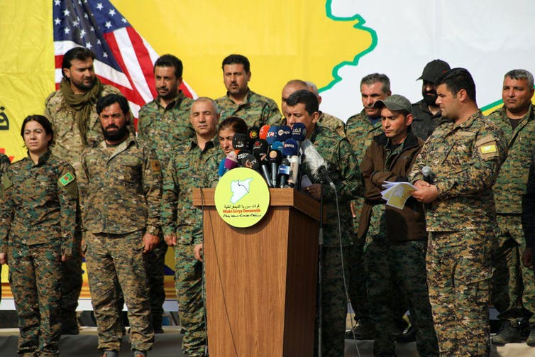 Syrian Democratic Forces commander Mazloum Abdi with other SDF officers celebrating military victory against ISIS in 2019.
