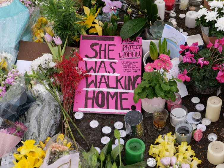 A pink sign with the handwritten message 'She was walking home', on the ground surrounded by flowers and candles