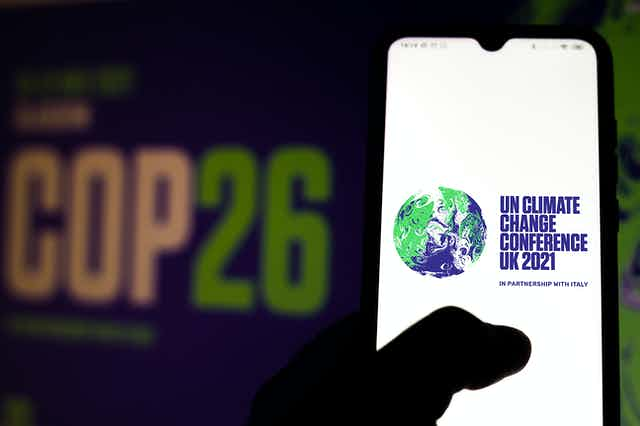 A hand holding a phone with the COP26 logo on it.