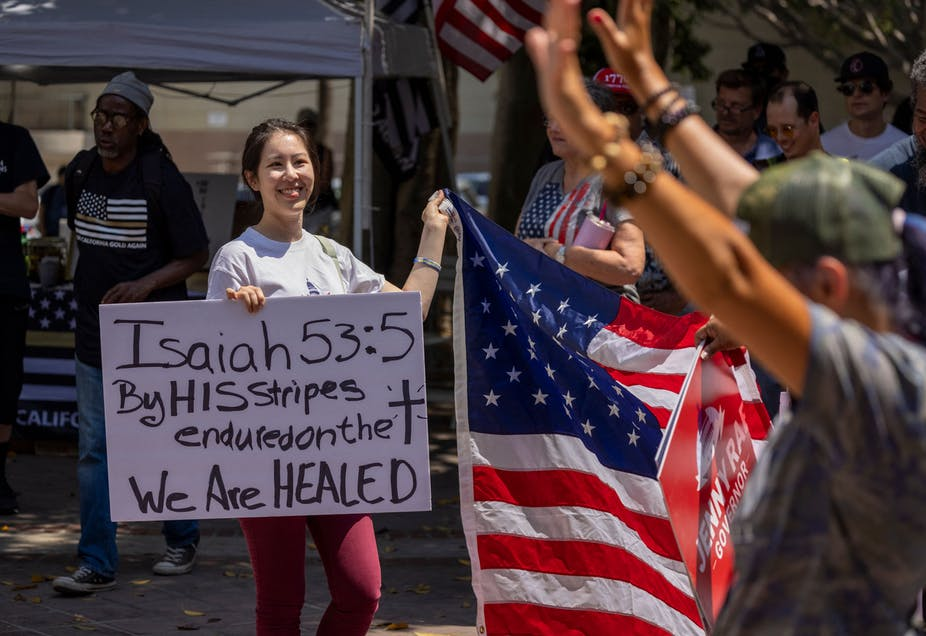 A woman holds a sign quoting Isaiah 53:5 in the Bible as anti-vaccination protesters pray and gather near City Hall in Los Angeles.