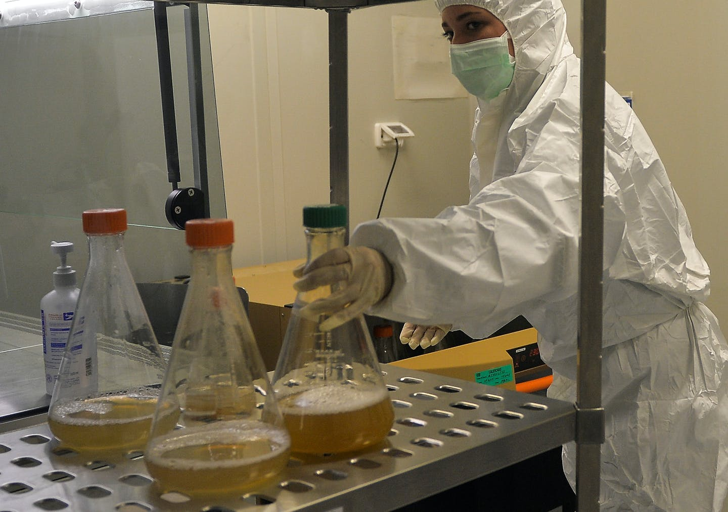 A woman in full body PPE reaches for a beaker containing a murky liquid.