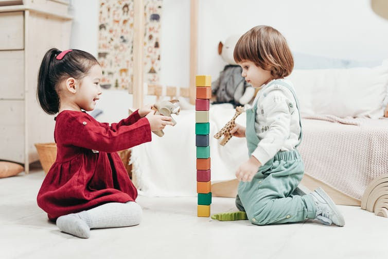 Two preschoolers play with blocks, one holding an elephant and one holding a giraffe, while sitting on the floor.