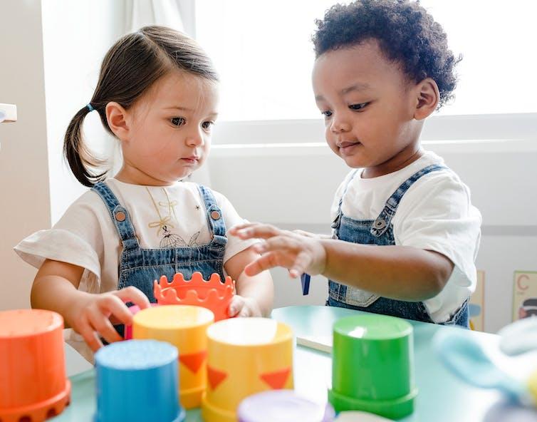 Two preschooler children in overalls play with stackable cups.