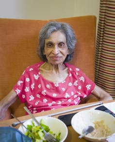 Indian older adult sitting in chair eating a meal.
