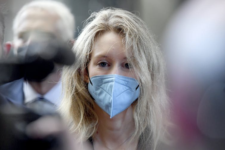 Elizabeth Holmes arrives at court wearing face mask and staring straight into camera as a few other faces and heads are blurred