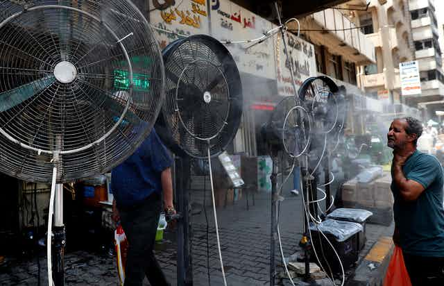 A man stands in front of floor fans on a street in Baghdad