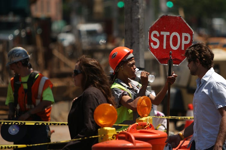 A construction worker, in a hard hat and drinking from a water bottle, holds a stop sign as people cross the street on a hot day in New York City.