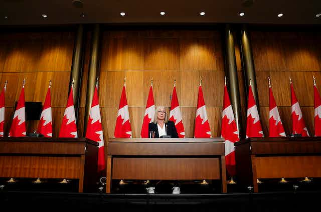 Patty Hajdu stands at a podium in front of a row of Canadian flags