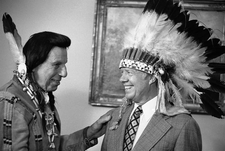 A man dressed in Native American clothes, Iron Eyes Cody, giving President Jimmy Carter a Native American headdress. Neither man was Native American.
