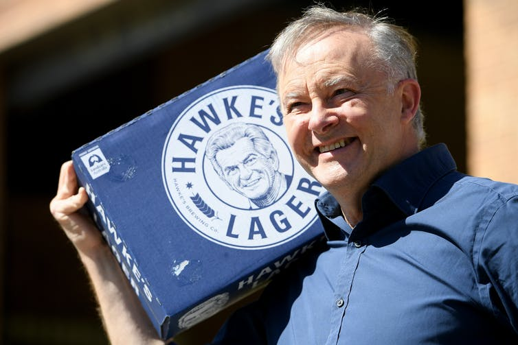 Anthony Albanese casually dressed carries a carton of Hawke's Lager on his shoulder.