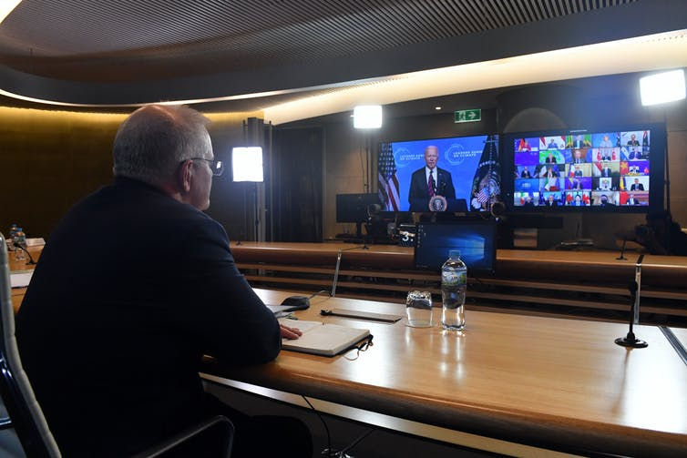 man sits in front of TV screens