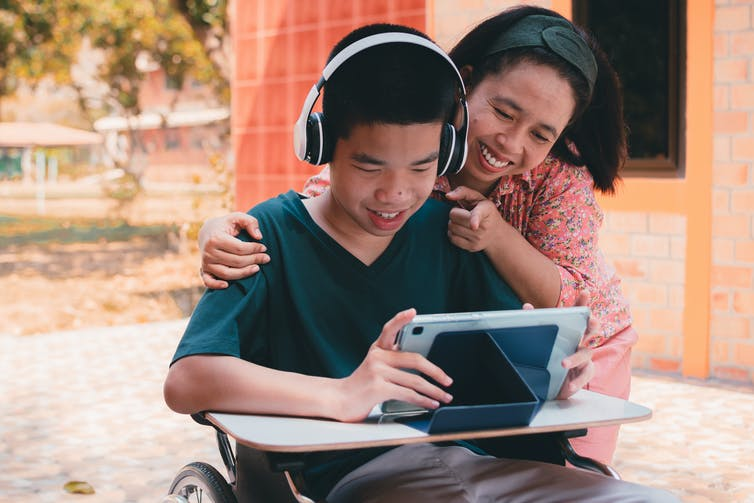 A student with disability on his Ipad, with Mum looking on behind him.