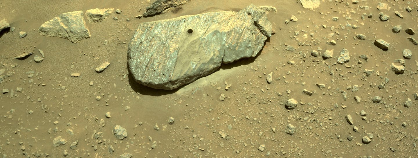 A rock on reddish brown surface with a circular hole drilled into the top.