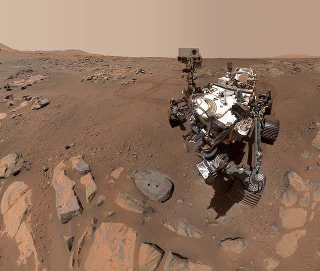 A large Mars rover next to a rock with two circular holes.