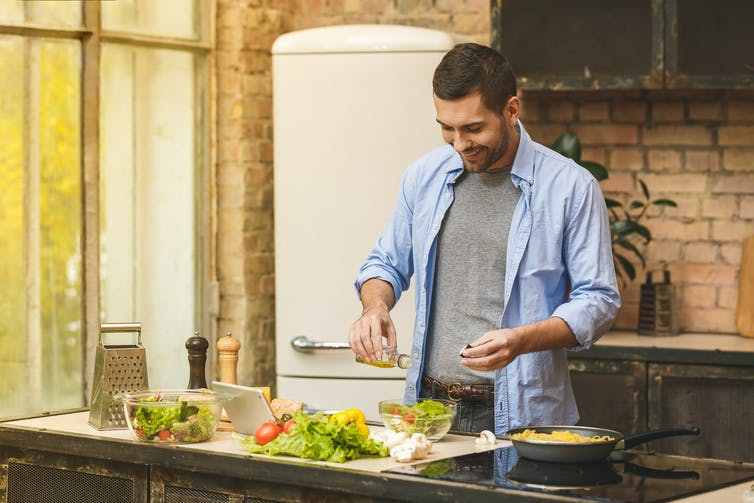 Young man in blue shirt puts salt in a salad bowl while cooking in the kitchen.