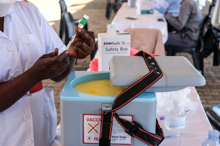 A health worker prepares a dose of COVID vaccine in Uganda