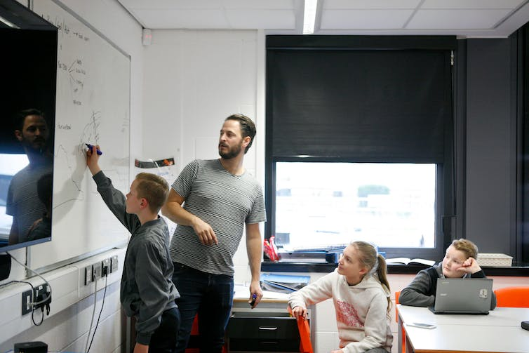 A teacher in a UK classroom with three students and lots of technology