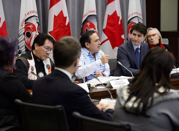 Justin Trudeau listens to Perry Bellegarde as he gestures during a meeting.