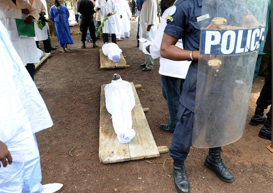 Corps dans des draps blancs sur des civières derrière un bouclier antiémeute siglé police.
