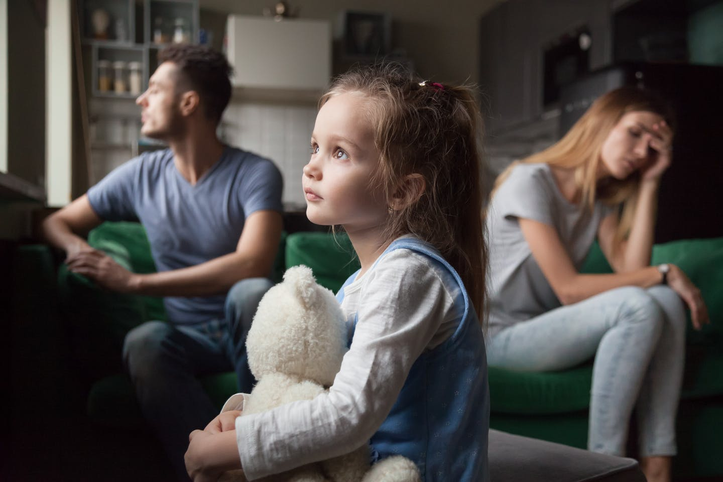 Child holding bear while parents look stressed out on couch.