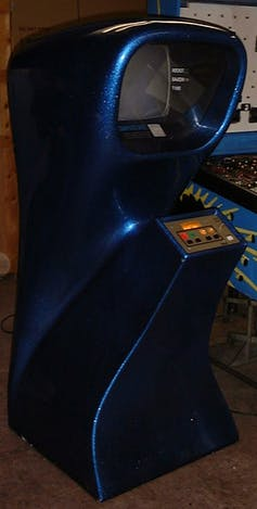 A vertical curvey arcade game console with four buttons on a control surface at the front and a hooded television screen at the top