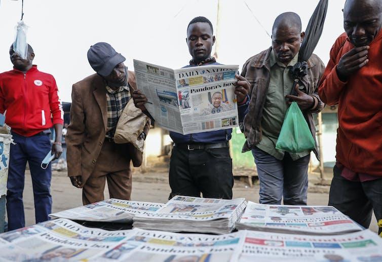 Un groupe d'hommes autour d'un stand à journaux