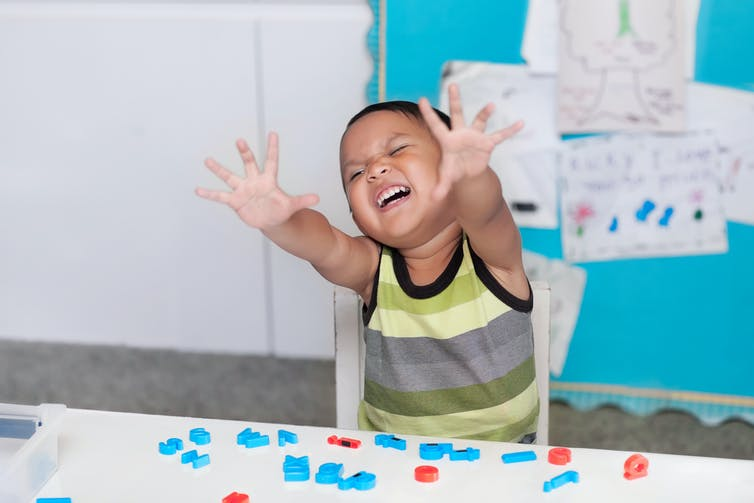 A boy in a classroom holding his hands out and yelling