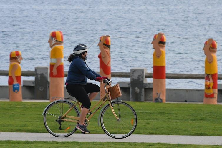 woman rides bike near water