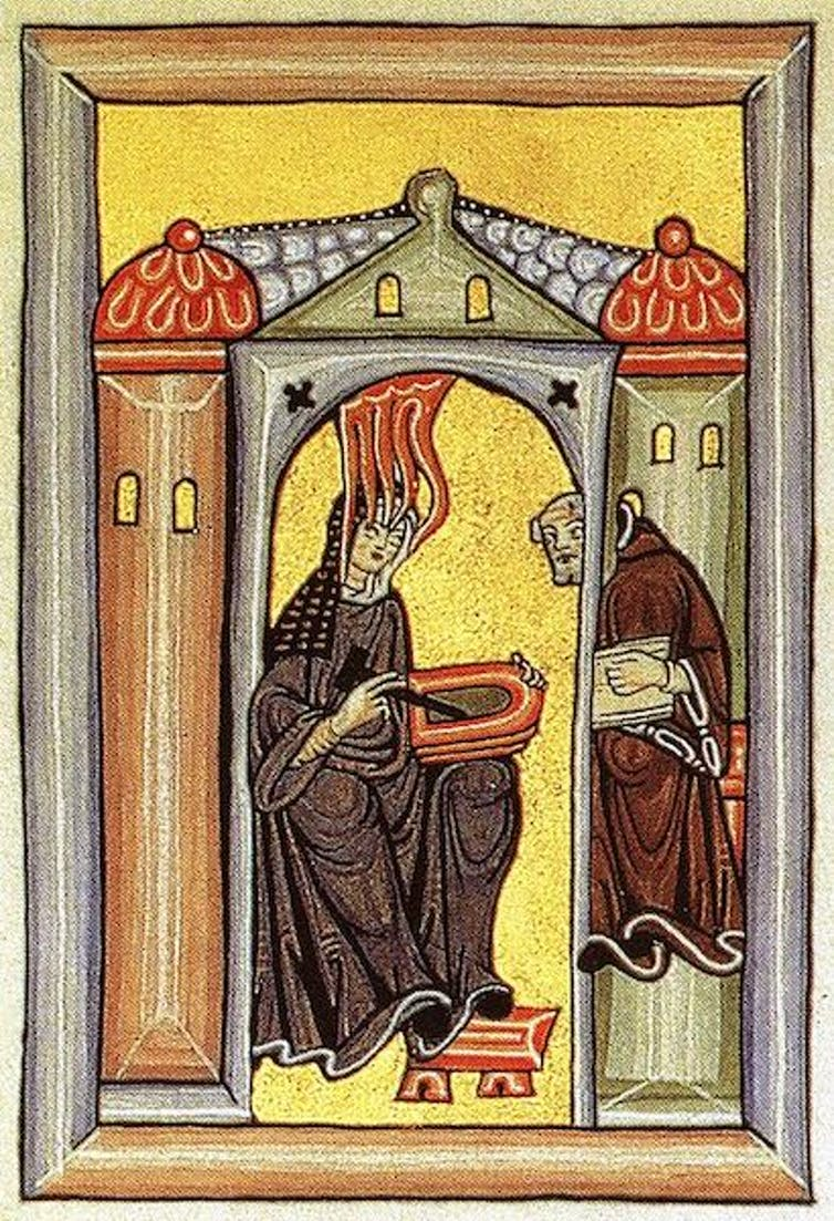 An illumination depicts Hildegard of Bingen experiencing a spiritual vision while dictating to a scribe.